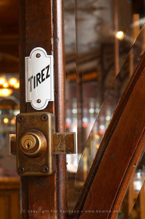 Detail of a door with a brass lock an enamel sign saying tirez (pull) and a facetted glass window The Bistrot du Peintre is an old fashioned Paris café cafe bar restaurant of art nouveau design with polished brass, mirrors and old signs