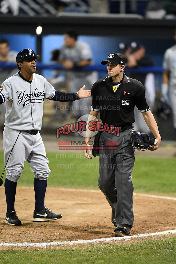 Staten Island Yankees coach Luis Figueroa (2) argues a call with umpire Justin Houser during a game against the Batavia Muckdogs on August 7, 2014 at Dwyer Stadium in Batavia, New York.  Staten Island defeated Batavia 2-1.  (Mike Janes/Four Seam Images)