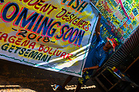 "A Colombian sign painter takes down a just-finished promotional banner in the sign painting workshop in Cartagena, Colombia, 14 April 2018. Hidden in the dark, narrow alleys of Bazurto market, a group of dozen young men gathered around José Corredor (""Runner""), the master painter, produce every day hundreds of hand-painted posters. Although the vast majority of the production is designed for a cheap visual promotion of popular Champeta music parties, held every weekend around the city, Runner and his apprentices also create other graphic design artworks, based on brush lettering technique. Using simple brushes and bright paints, the artisanal workshop keeps the traditional sign painting art alive."