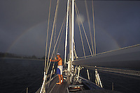 Man standing deck of sailboat with rain and rainbow in background, Hanalei Bay, Kauai. Hawaii