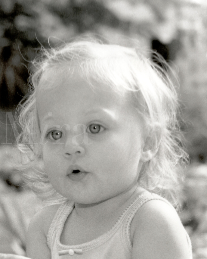 Black and white image of a one year old blonde girl with blue eyes showing amazement.