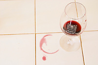 In the tasting room a glass of Mourgues de gres on a tiled white tabletop with a red ring of spilled wine. Chateau Mourgues du Gres Grès, Costieres de Nimes, Bouches du Rhone, Provence, France, Europe