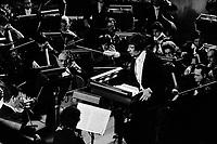 """Halle aux Grains à Toulouse. Le 11 Décembre 1977. Vue d'ensemble en plongée d'une partie de l'ochestre du capitole, avec en son centre le chef d'orchestre Michel Plasson dirigeant l'opéra """"Fidélio"""" de Ludwig Van Beethoven."""