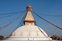 Bodhnath, Nepal.  The All-Seeing Eyes of the Buddha Gaze out from above the Stupa of Bodhnath, a center of Tibetan Buddhism, near Kathmandu.  The 13 tapering levels above the dome represent the 13 stages of perfection leading to nirvana.  Saffron stain decorates the dome.