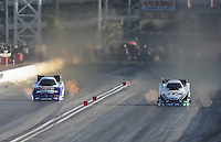 Mar. 31, 2012; Las Vegas, NV, USA: NHRA funny car driver Mike Neff (right) races alongside Matt Hagan during qualifying for the Summitracing.com Nationals at The Strip in Las Vegas. Mandatory Credit: Mark J. Rebilas-