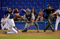 Tampa Yankees catcher Francisco Arcia tags out Andy Burns #9 as umpire Fernando Rodriguez gets in position during a game against the Dunedin Blue Jays on April 11, 2013 at Florida Auto Exchange Stadium in Dunedin, Florida.  Dunedin defeated Tampa 3-2 in 11 innings.  (Mike Janes/Four Seam Images)