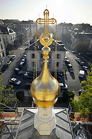 """Switzerland. Geneva.The Russian Church (full name: Cathédrale de l'Exaltation de la Sainte Croix) is designed in a Byzantine Moscovite style. The church is a lovely 19th-century Russian Orthodox church topped with golden onion domes. The roof and all onion domes underwent a complete revival restoration. The newly restored bulb from the bell tower is back on the church and gilded with golden leaves. The term gilding covers a number of decorative techniques for applying fine gold leaf to solid surfaces such as onion domes and crosses. A gilded object is also described as """"gilt"""". The Russian church serves today not only the Russian community but also Bulgarians, Serbs, Coptic Christians and other Orthodox worshippers who do not have their own church in Geneva. An onion dome is a dome whose shape resembles an onion. Such domes are often larger in diameter than the drum upon which they sit, and their height usually exceeds their width. These bulbous structures taper smoothly to a point. 9.2.2017 © 2017 Didier Ruef"""