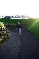 Superintendent Josh Lewis rakes up the deep pot bunker. Chambers Bay Golf Course in University Place, Washington will host the 2015 U.S. Open in June 2015. Photo by Daniel Berman for Golf Course Management Magazine.