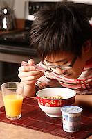 MODEL RELEASED PHOTO.<br /> A fourteen (14) year old asian male teenager, from China eat a breakfast made of cereal, yogourt and orange juice<br /> <br /> Un jeune adolescent de quatorze (14) ans d'origine Chinoise mange un dŽjeuner composŽ de cŽrŽales, yogourt et jus d'oranges. <br /> <br /> Photo : Pierre Roussel / Images Distribution