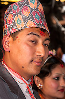 Nepal, Patan.  Groom at Wedding Ceremony in Golden Temple (Kwa Baha).  He wears a dhaka topi (traditional Nepalese hat) and a  tika, or tilak, of red kumkuma powder on his forehead.