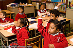 Parochial School Bronx New York  Kindergarten children raising hands horizontal