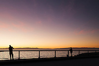 Two anglers on a bridge, casting lines into San Francisco Bay, while the warm glow of sunset envelops the sky, water and them.