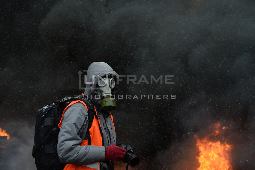A photo-journalist wearing a gas mask while reporting from the barricades to protect himself by tear gas fired by the police during protests. Kiev, Ukraine. Jan 01, 2014. (Photo by Msyslav Chernov / UnFrame)
