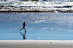 Female child running on beach.  Silhouette, Kalaloch Beach in Olympic National Park, Washington.  Beaches in the Kalaloch area of Olympic National Park, identified by trail numbers, are remote and wild.  Olympic Peninsula, Olympic Mountains, Olympic National Park, Washington State, USA.