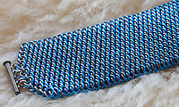 """A blue and silver dragonscale weave maille bracelet.  It's made from saw cut 18 gauge 1/4"""" ID blue anodized aluminum rings and saw cut 19 gauge 5/32"""" ID bright aluminum rings.  The clasp is a gunmental plated slide clasp.  The bracelet is on a sheepskin rug.   Handmade by Michelle."""