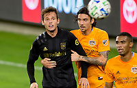 CARSON, CA - OCTOBER 28: Zarek Valentin #4 of the Houston Dynamo battles holding Danny Musovski #16 of the Los Angeles FC during a game between Houston Dynamo and Los Angeles FC at Banc of California Stadium on October 28, 2020 in Carson, California.