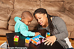 Two year old toddler boy with mother watching as she shows him how picture blocks form a picture