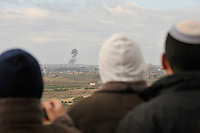 Israelis look on as a Hamas target is bombed by Israeli jets (not seen), in the Gaza Strip. Israeli forces began an air offensive against Hamas in Gaza on 27/12/2008, which quickly escalated into an offensive by land, sea and air, in retaliation against Palestinian rockets fired into Israel. After eight days of bombardment, leaving over 400 Palestinians and four Israelis dead, Israeli tanks entered Gaza on 04/01/2009...