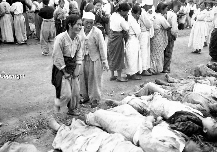Koreans from Hamhung identify the bodies of some 300 political prisoners who were killed by the North Korean Army by being forced into caves which were subsequently sealed off so that they died of suffocation.  October 19, 1950.  Lt. Winslow. (Army)<br /> NARA FILE #:  111-SC-351359<br /> WAR & CONFLICT BOOK #:  1508