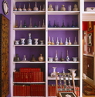 A collection of blue and white rosewater sprinklers is displayed on simple white shelving against a dramatic purple wall
