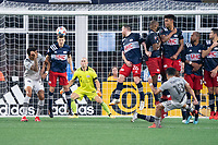 FOXBOROUGH, MA - JULY 25: Scott Caldwell #6 of New England Revolution heads a shot on goal by Joaquín Torres #18 of CF Montreal during a game between CF Montreal and New England Revolution at Gillette Stadium on July 25, 2021 in Foxborough, Massachusetts.