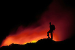 Silhouette of a man watching lava flow, Hawaii, USA.