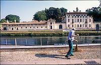 Cassinetta di Lugagnano (Milano). Uno spazzino al lavoro lungo il Naviglio Grande di fronte a Villa Visconti  --- Cassinetta di Lugagnano (Milan). A street cleaner at work along the canal Naviglio Grande in front of Villa Visconti