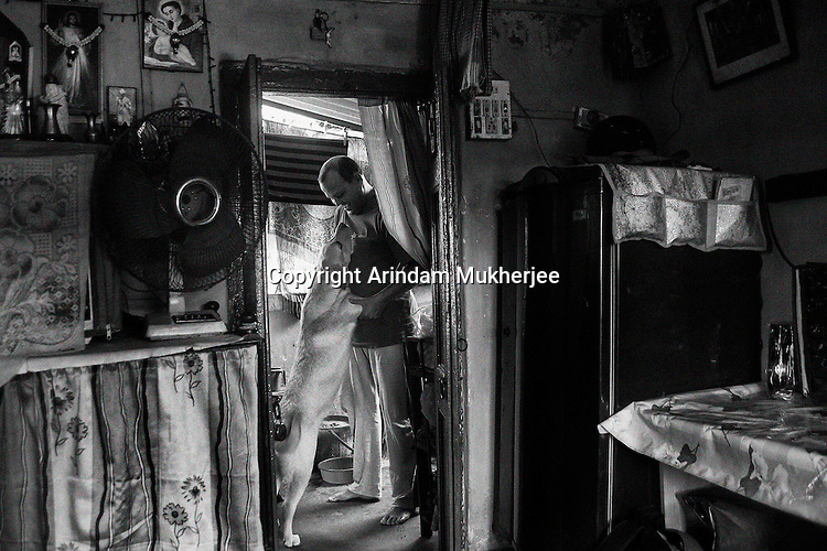 Robert Smith, a dog trainer by profession plays with his pet in his house in Kolkata.