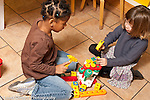 Education preschool 3-4 year olds two girls playing together with toy plastic hammers and construction toy horizontal