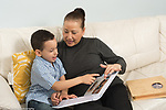 4 year old boy sitting with grandmother looking at photo album talking