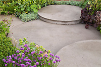Chive herbs and other plants around circular patio in several level tiers