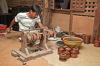Myanmar, Burma. Bagan.  Lacquerware Workshop, Man Polishing Lacquer Bowls.