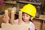 Education Preschool 4 year olds girl talking to herself as she builds block structure wearing pretend play construction hat