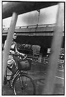 A young lady cyclist navigates between the concrete boulevards and overpasses of Beijing...PHOTO BY WANG TONG / SINOPIX