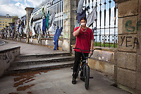 Roberto bikes in front of the Navantia shipbuilding compound, where fired workers have hung their uniforms in protest. Roberto works as a lumberjack because he couldn't find a job related to his studies. Ferrol, Spain.