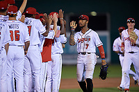 Lansing Lugnuts DJ Neal (7) high fives teammates after a Midwest League game against the Burlington Bees on July 18, 2019 at Cooley Law School Stadium in Lansing, Michigan.  Lansing defeated Burlington 5-4.  (Mike Janes/Four Seam Images)