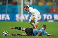 Wayne Rooney of England jumps Alvaro Pereira of Uruguay