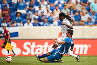 Trinidad and Tobago midfielder Keon Daniel (19) shoots and scows under pressure from El Salvador defender Steven Purdy Ramos (4) during a CONCACAF Gold Cup group B match at Red Bull Arena in Harrison, NJ, on July 8, 2013.