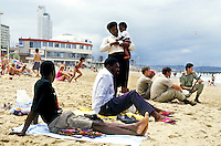 Beaches open to all, black and white. AWB members (Afrikar Weerstandsbeweging) (Afrikaner Resistance Movement) - sit on the beach near a black family after a demonstration in the city.