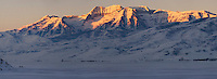 Panoramic view of Mount Timpanogos and surrounding peaks at sunrise, with dramatic early light illuminating a large cirque. A group of ice fishermen circle a hole on Deer Creek reservoir lower left. Wasatch Range, Utah, USA.