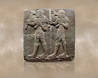 Photo of Hittite monumental relief sculpted orthostat stone panel of a Procession Basalt, Karkamıs, (Kargamıs), Carchemish (Karkemish), 900-700 B.C.  Anatolian Civilisations Museum, Ankara, Turkey. Young male servants of Kubaba while carrying sacrificial animals on their shoulders. <br /> <br /> Against a brown art background.