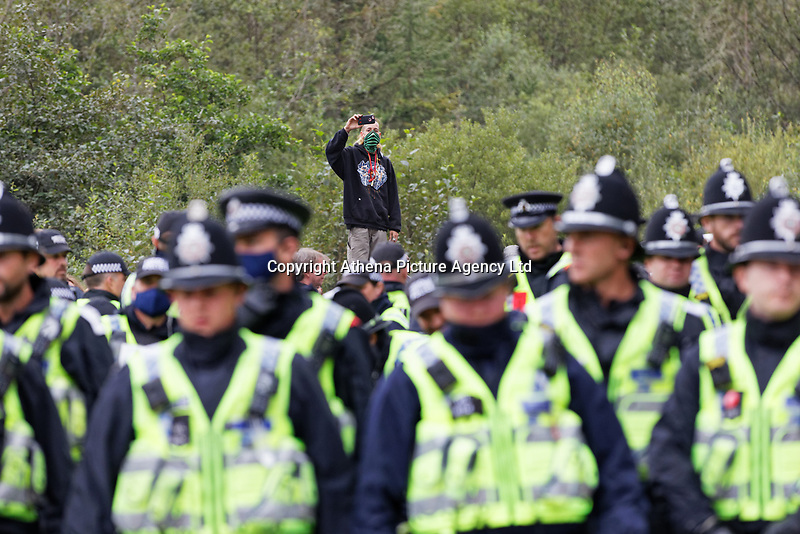 Pictured: A young reveller takes a picture of the police officers. Monday 31 August 2020<br /> Re: Around 70 South Wales Police officers executed a dispersal order at the site of an illegal rave party, where they confiscated sound gear used by the organisers in woods near the village of Banwen, in south Wales, UK.