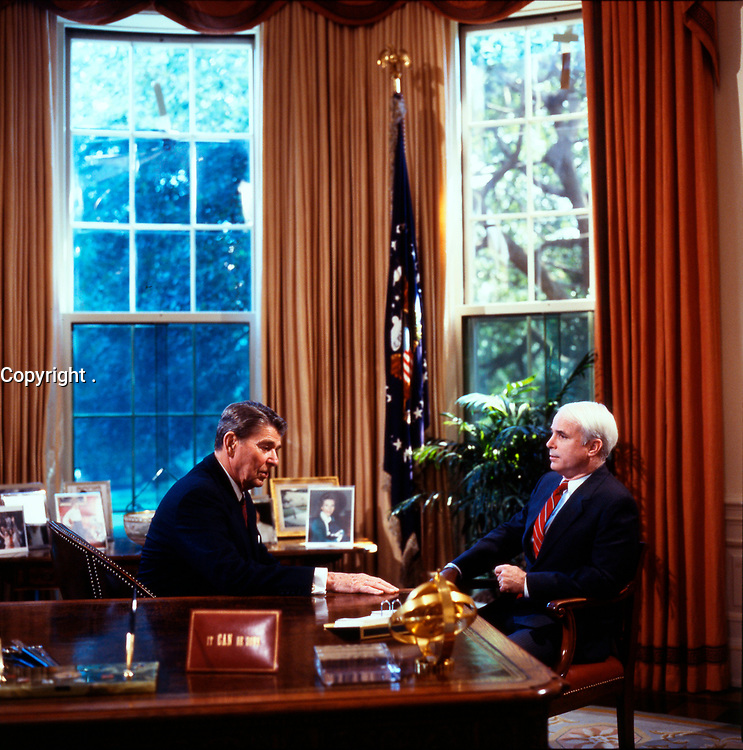 """Undated File photo  (circa 1983)<br /> US President Ronald Reagan (L) discuss with<br /> US Republica Senator John Sidney McCain III  (R) <br /> <br /> <br /> <br /> John Sidney McCain III (born August 29, 1936) is the senior United States Senator from Arizona and presumptive Republican Party nominee for President of the United States in the 2008 election.<br /> <br /> McCain graduated from the United States Naval Academy in 1958 and became a naval aviator, flying ground-attack aircraft from aircraft carriers. During the Vietnam War, he nearly lost his life in the 1967 USS Forrestal fire. Later that year while on a bombing mission over North Vietnam, he was shot down, badly injured, and captured as a prisoner of war by the North Vietnamese. He was held from 1967 to 1973, experiencing episodes of torture and refusing an out-of-sequence early repatriation offer; his war wounds would leave him with lifelong physical limitations.<br /> <br /> He retired from the Navy as a captain in 1981 and, moving to Arizona, entered politics. He was elected to the U.S. House of Representatives in 1982. After serving two terms, he was elected to the U.S. Senate in 1986, winning re-election easily in 1992, 1998, and 2004. While generally adhering to conservative principles, McCain has gained a media reputation as a """"maverick"""" for disagreeing with his party on several key issues. After being investigated in a political influence scandal of the 1980s, as a member of the """"Keating Five"""", he made campaign finance reform one of his signature concerns, which eventually led to the passage of the McCain-Feingold Act in 2002. He is also known for his work towards restoring diplomatic relations with Vietnam in the 1990s, and for his belief that the war in Iraq should be fought to a successful conclusion in the 2000s. McCain has chaired the powerful Senate Commerce Committee, and has been a leader in seeking to rein in both pork barrel spending as well as Senate filibusters of judicial nominations"""