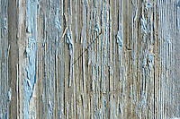 Detail of peeling paint on wood building.