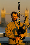 CITY OF LONDON, A LONE BUSKER PLAYING BAGPIPES FOR COMMUTERS ON THEIR WAY HOME FROM WORK ON LONDON BRIDGE WITH TOWER BRIDGE IN THE BACKGROUND, 1992 1990s UK