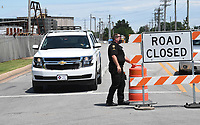 Springdale police officer Rick Olcott moves a traffic barrel so fire personnel can exit after responding to an ammonia leak inside Cargill Meat Solutions building on Jefferson St. in Springdale Thursday July 30, 2020 Visit nwaonline.com/200731Daily/ for photo galleries. (NWA Democrat-Gazette/J.T. Wampler)