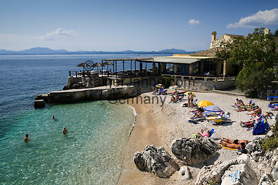 Greece, Corfu, Nisaki (Nissaki): Sun bathers on beach with clear water