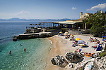 Greece, Corfu, Nisaki (Nissaki): Sun bathers on beach with clear water