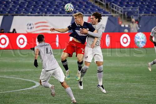 20th November 2020; Foxborough, MA, USA;  New England Revolution forward Adam Buksa heads the ball clear with Montreal Impact defender Luis Binks on his back during the MLS Cup Play-In game between the New England Revolution and the Montreal Impact