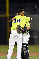 Closer Darwin Ramos (34) and catcher Scott Manea (25) of the Columbia Fireflies hug after recording the final out in a game against the Augusta GreenJackets on Friday, April 6, 2018, at Spirit Communications Park in Columbia, South Carolina. Columbia won, 7-2. (Tom Priddy/Four Seam Images)
